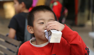 Kid drinking milk out of a small carton